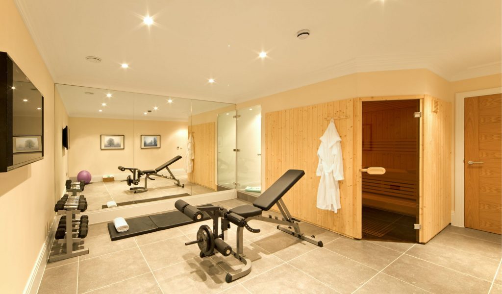 amazing basement gym with huge wall mirror and sauna room - basement remodeling ideas