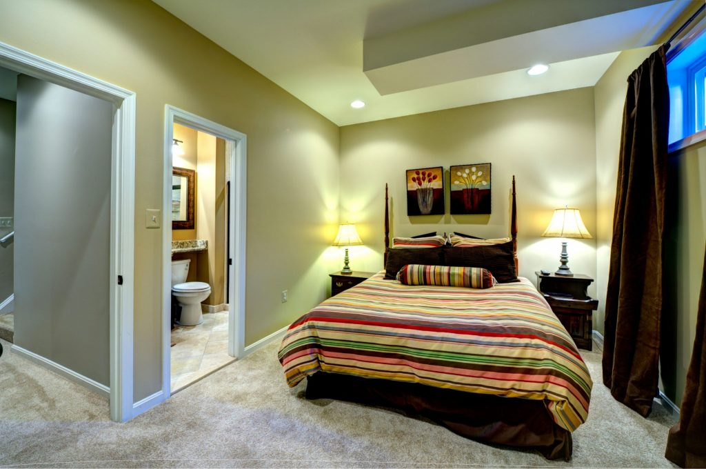 amazing bedroom in custom basement with green wall painting and floor carpet - toronto basement renovation