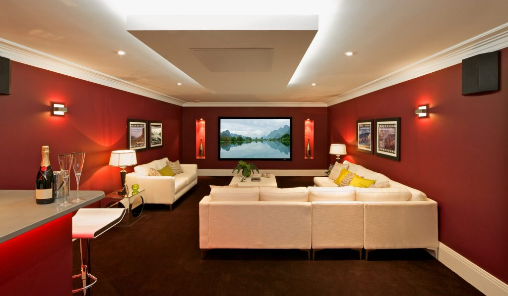 custom basement with red wall painting and crown moulding - basement renovation ideas