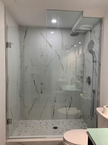 walk in shower with glass enclosure and marble tile wall decor - basement design ideas