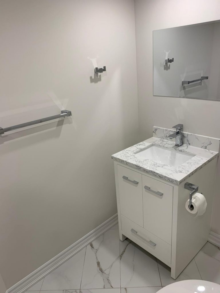 modern basement bathroom with wall mirror and small white vanity - basement renovation mississauga