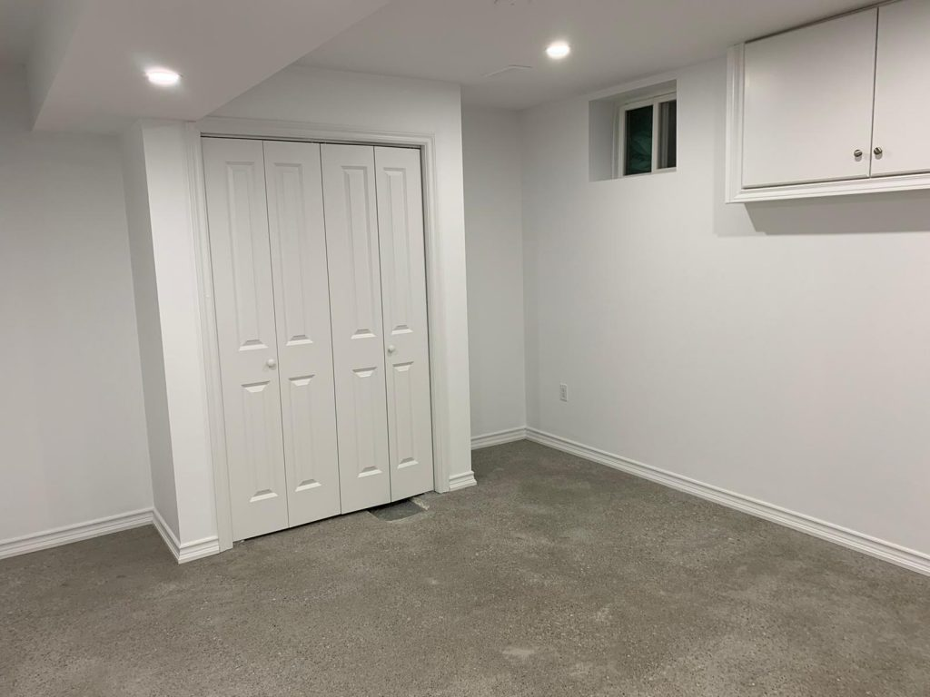 basement bedroom with build in closet and floor carpet - basement reno