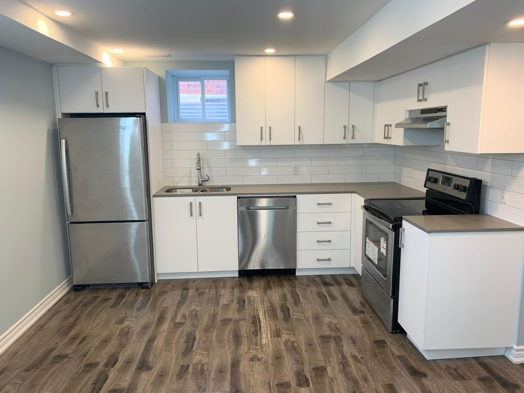 modern basement kitchen with wooden floor and white kitchen cabinets - basement company