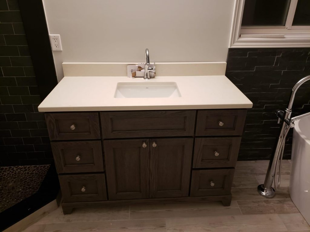 brown vanity and freestanding bathtub in basement bathroom - basement finishing toronto