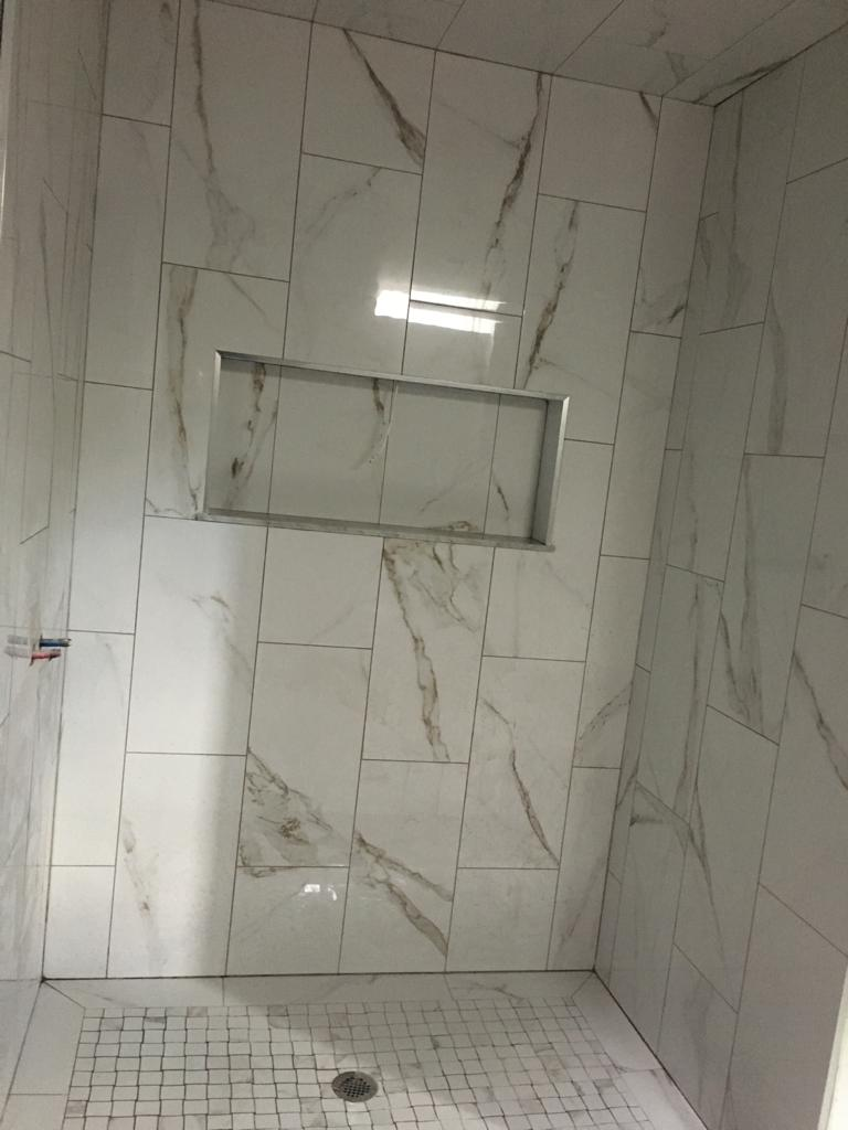 build in storage space and custom wall marble tile decor in lucury basement bathroom - basement renovation brampton