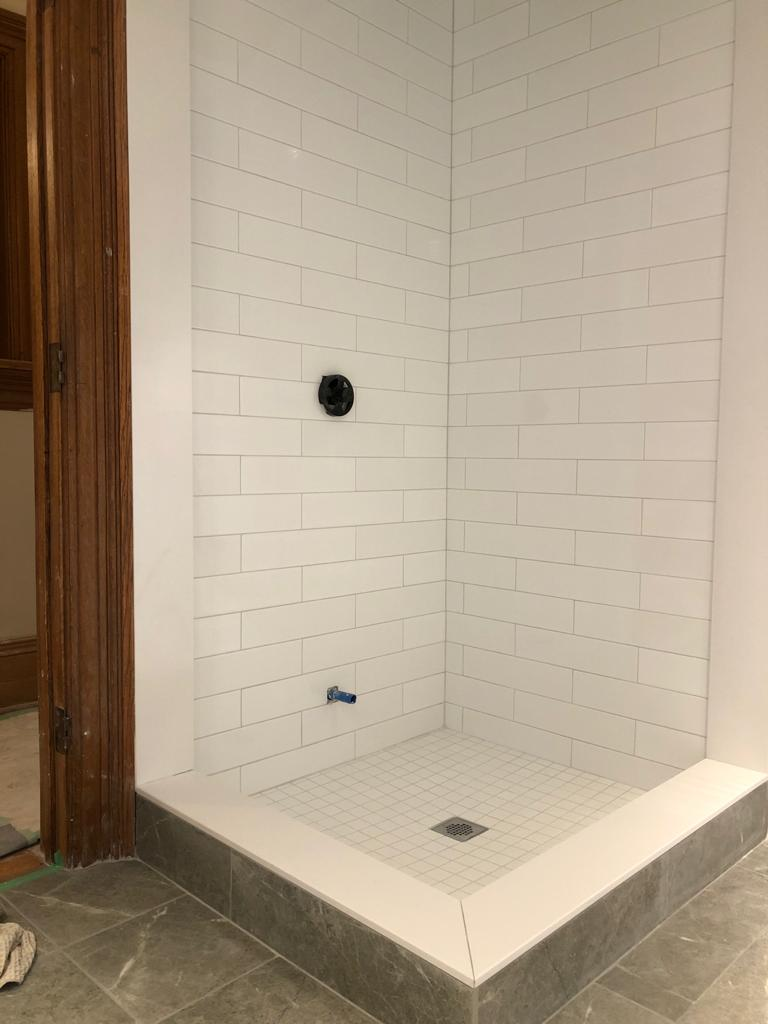 shower base and wall trim in custom basement bathroom - basement contractors
