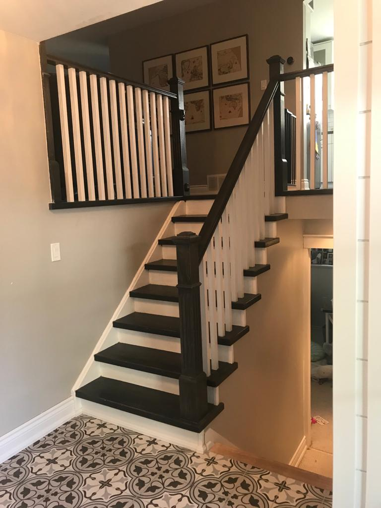 home staircase with wooden railings and black and white stairs - basement remodeling toronto