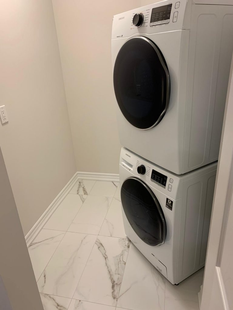 small basement laundry room with baseboard trim and appliances - DRV basement company GTA